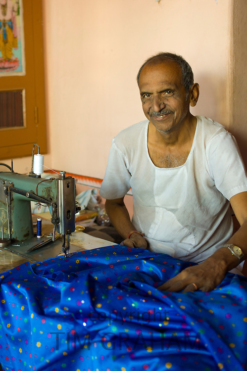 Indian tailor uses sewing machine to make silk clothing in Narlai village in Rajasthan, India