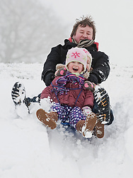 © Licensed to London News Pictures. 05/02/2012. Dunstable, UK. Twins Sophia and Fabianna Kabelis aged 4, from Dunstable sledding with their dad Waldemar Kabelis  on a snow covered Dunstable Downs in Bedfordshire, on February 5th, 2012. Photo credit : Ben Cawthra/LNP