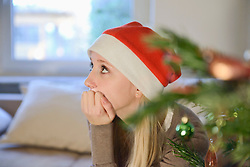 Thoughtful teenage girl in front of christmas tree