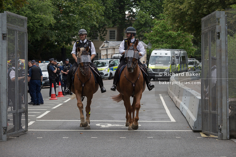 Mounted police officers leave the temporary perimeter fence encircling Winfield House, the official residence of the US Ambassador during the visit to the UK of US President, Donald Trump, on 12th July 2018, in Regent's Park, London, England.