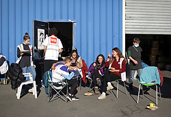 18 November 2020. Care4Calais - Calais, France.<br /> Volunteers gather for lunch at the volunteer run migrant refugee charity Care4Calais distribution centre near Calais. The British charity provides meals, clothing, haircuts, charging stations for phones, hot drinks, tents, blankets and a wide range of goods and services to help migrant refugees struggling to survive on the streets of Calais where they are continually harassed and moved on by authorities. <br /> Photo©; Charlie Varley/varleypix.com