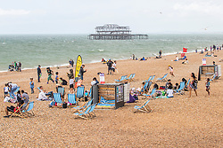 © Licensed to London News Pictures. 20/07/2019. Brighton, UK. Grey clouds hang over the Brighton and Hove beach as a handful of visitors brave the weather to spend time on the beach in Brighton and Hove. Photo credit: Hugo Michiels/LNP