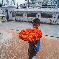 A youngster sells sweet breads at Bodh'nath Stupa in Kathmandu, Nepal, 1996.