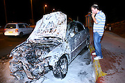 Man stands next to his burnt car. The car caught fire due to a traffic accident