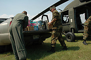 national guardsmen are seen emptying supplies  from the governor of Mississippis helicopter  to a transport truck on the way to Bay St. Louis Mississippi Sunday Sept. 4,2005 The governor went to Bat St. Louis high School  where a shelter was set up in their gym and distributed supplies and water to the refugees..(photo/Suzi Altman)