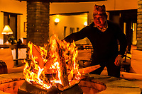 A staff member lights a fire in a firepit in the bar of the Tiger Mountain Pokhara Lodge, above Pokhara, Nepal.