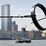 Nederland Rotterdam 9 juli 2010 20100709 Stadsgezicht Kop van Zuid / Noordereiland, rivier de Maas.    Op de voorgrond zitten meeuwen in een stalen kunstwerk, een lijn met daaraan een circelvormig object en vaart een motorboot over de rivier de Maas. Op de achtergrond  appartementen op het Noordereiland en o.a. hoogbouw nieuwbouw het hoogste kantoorgebouw van Nederland De Maastoren op de Kop van Zuid. , stadachtig, stadgezicht, stads, stadsaanzicht, stadsbeeld, stadscentrum, stadsdeel, stadse, stadsgezicht, stadshaven, stadshavens, stadslandschap, stadsontwikkeling, stadsuitbreiding, stadsuitbreidingslocaties, stadsvernieuwing, stalen, stedebouw, stedelijk gebied, stedelijk lokatie, stedelijke, stedelijke planning, stedelijke vernieuwing, steden, stedenbouw, steeds, steedse, stilleven, straatbeeld, straatgezicht, street scenery, streetscene, sunshine, the netherlands, the sky is the limit, toren, torens, tower, uitbreidingsgebieden, urban landscape, urbanisatie, urbanisering, urbanisme, urbanistisch, urbanistische, vaart, varen, vastgoed, vernieuwing, vernieuwing stedelijk, vervoer over water, vessel, vogel, vogels, vrij, water, water level, Water Management Authority, waterbeheer, Waterbeheerplan, watergang, waterhuishouding, waterlevel, watermanagement, watermassa, waterniveau, Waterpeil, waterplan, wolkenkrabber, wolkenkrabbers, wonen aan het water, woningaanbod, woningblok, woningblokken, woningen, woonblok, woonblokken, zonnig weer, , sculpture, sculpturen, sculptuur, skyline, Skyscraper, skyscrapers, staal, staaldraad, staaldraden, stad Foto: David Rozing