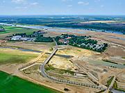 Nederland, Limburg, Gemeente Horst aan de Maas.; 27-05-2020; Ooijen, nieuwe brug over de (uitgegraven) Oude Maasarm tussen Ooijen en Wanssum. Boven het midden het recreatiepark Kasteel Ooijen. Bij hoogwater kan de de oude rivier weer mee gaan stromen. Onderdeel van <br /> Gebiedsontwikkeling  Ooijen en Wanssum, waaronder aanleg van een  hoogwatergeul, weerdverlaging en natuurontwikkeling.<br /> Ooijen, new bridge over the (excavated)  old branch of the Meuse. On the left the recreation park Kasteel Ooijen. At high tide, the old river can flow again.<br /> <br /> luchtfoto (toeslag op standard tarieven);<br /> aerial photo (additional fee required)<br /> copyright © 2020 foto/photo Siebe Swart