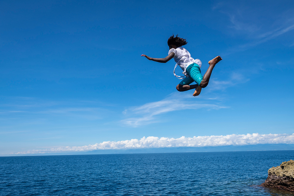 A teenage girl enjoys a Sunday afternoon by jumping off a rocky outcrop into the sea in the town of Madang, Papua New Guinea. (June 30, 2019)