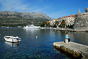 Child (9 years old) sitting on stone bollard on stone jetty, Korcula old town in background. Korcula old town, island of Korcula, Croatia