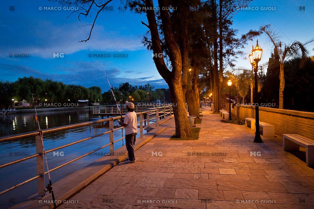 ANOCHECER EN UNO DE LOS NUMEROSOS CANALES DEL DELTA DEL RIO PARANA, HOMBRE PESCANDO, COSTANERA DE DIQUE LUJAN, PROVINCIA DE BUENOS AIRES, ARGENTINA (PHOTO © MARCO GUOLI - ALL RIGHTS RESERVED)