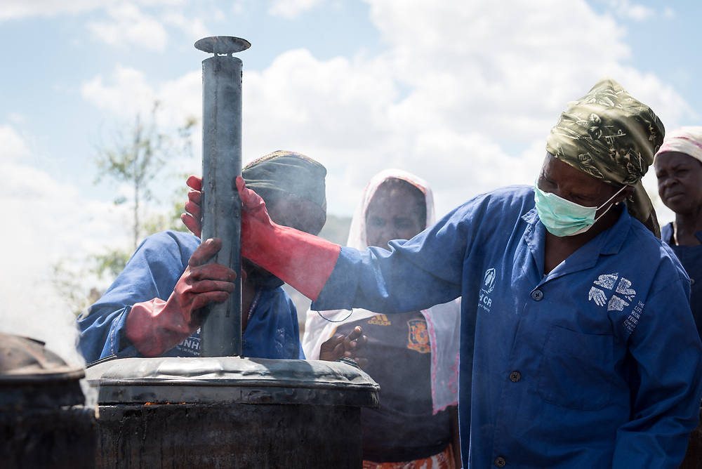 30 May 2019, Mokolo, Cameroon: Aisha Bukar (left) and Hawa Harona (right) mount the lid onto a metal container in which biomass is burnt, in preparation to become charcoal. At the Minawao camp for Nigerian refugees, degradable and non-degradable waste are separated, so that biomass can be burnt in metal containers, processed and finally transformed into charcoal briquettes as a source of recycled energy to be used as firewood for cooking. With the support of an environment monitor  from the Lutheran World Federation World Service programme, the full process from waste to charcoal is managed and run by the refugees themselves. The Minawao camp for Nigerian refugees, located in the Far North region of Cameroon, hosts some 58,000 refugees from North East Nigeria. The refugees are supported by the Lutheran World Federation, together with a range of partners.