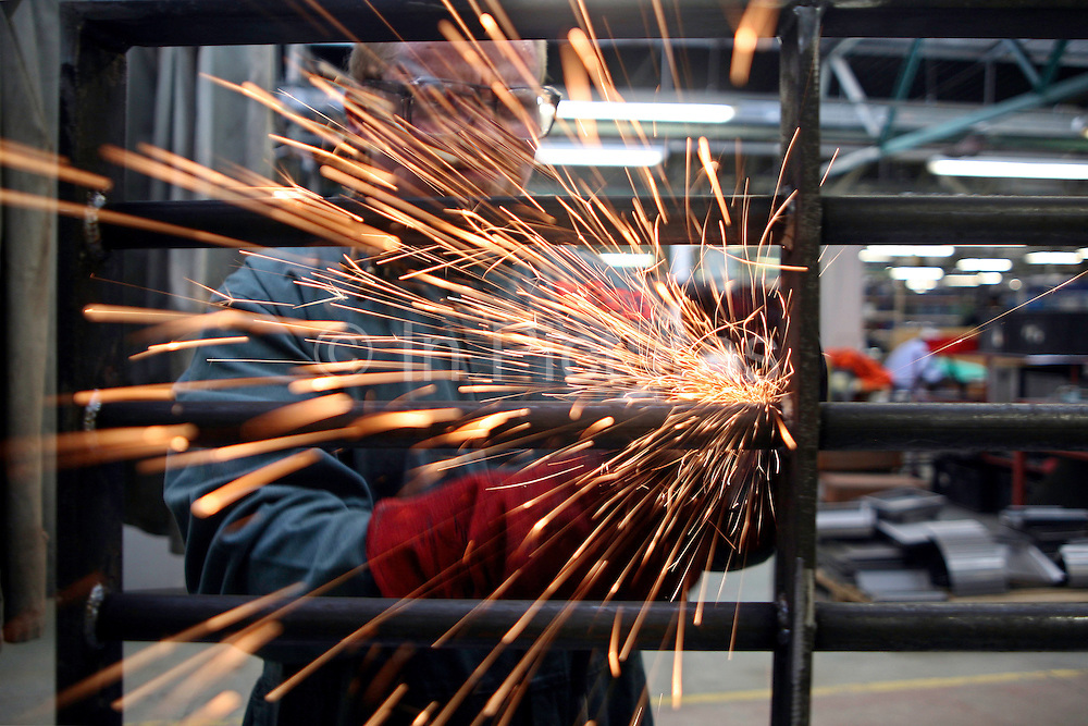 A prisoner at Coldingley makes prison gates in the steel workshop..HMP Coldingley, Surrey was built in 1969 and is a Category C training prison. Coldingley is focused on the resettlement of prisoners and all prisoners must work a full working week within the prison. Its capacity is 390 prisoners.