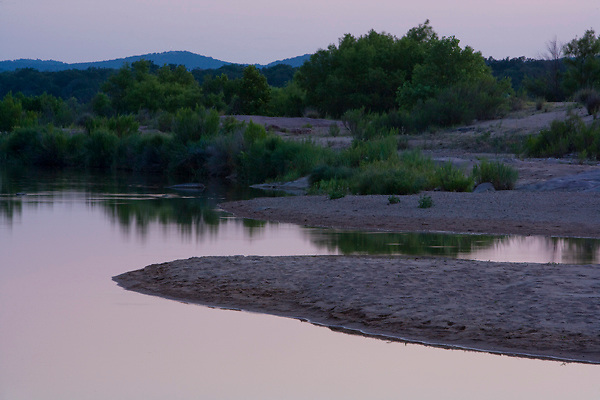 Stock photo of a sunset along the quiet water of the Llano River in the Texas Hill Country