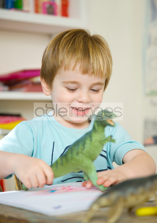 Close up of a smiling boy playing with a toy dinosaur