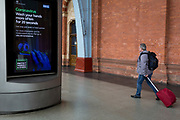 As the UK government urged that all Britons should avoid non-essential travel abroad in order to combat the Coronavirus pandemic in Britain, rail passengers pass-by a digital public information ad from the government and the NHS (National Health Service) tells the public to wash their hands thoroughly, at St. Pancras rail station, the London terminus for Eurostar services to mainland Europe, on 17th March 2020, in London, England.