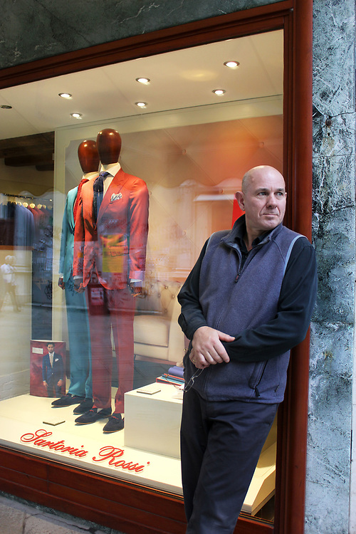 Middle aged man standing in from of trendy Italian men's cloth shop, Venice, Italy.