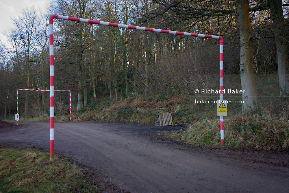 Height restriction caution sign and poles in a north Somerset woodland.
