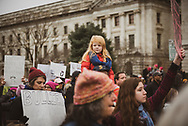 Washington DC, USA - January 21, 2017: A young girl rides on her father's shoulders, part of a large crowd walking down the National Mall during the Women's March in Washington DC.