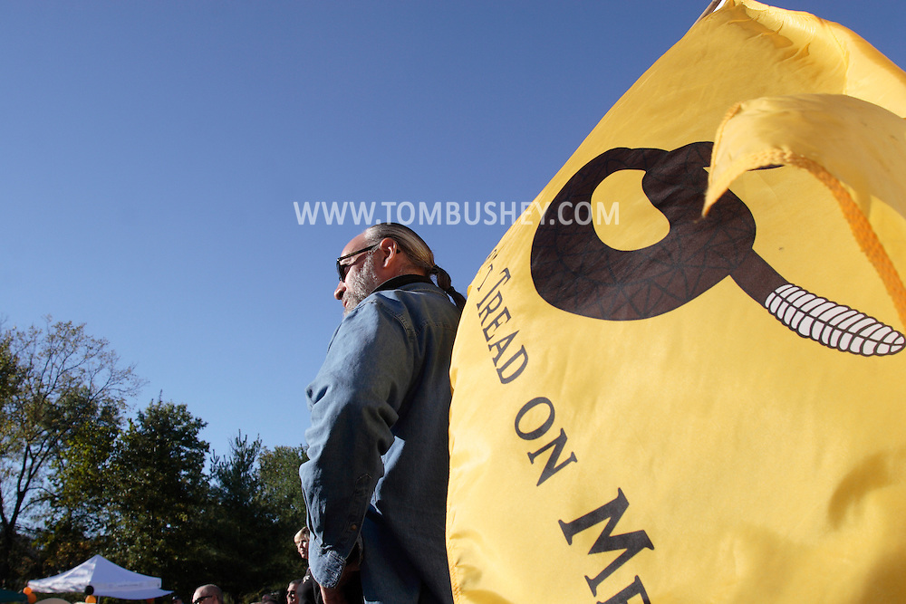 """Middletown, New York - A man holds a """"Don't Tread on Me"""" flag during an Orange/Sullivan County 912 Tea Party forum with Republican gubernatorial candidate Carl Paladino in the parking lot outside party headquarters on Oct. 9, 2010."""