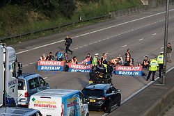 Ockham, UK. 21st September, 2021. Insulate Britain climate activists block the clockwise carriageway of the M25 between Junctions 9 and 10 as part of a campaign intended to push the UK government to make significant legislative change to start lowering emissions. Both carriageways were briefly blocked before being cleared by Surrey Police. The activists are demanding that the government immediately promises both to fully fund and ensure the insulation of all social housing in Britain by 2025 and to produce within four months a legally binding national plan to fully fund and ensure the full low-energy and low-carbon whole-house retrofit, with no externalised costs, of all homes in Britain by 2030.