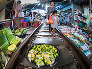 27 SEPTEMBER 2016 - BANGKOK, THAILAND: A mother and her daughter walk along the tracks, past a stand selling limes in the market in the train station in Samut Songkhram. The train from Baen Laem to Samut Songkhram (Mae Khlong) recently resumed service. The 33 kilometer track was closed for repair for almost a year. In Samut Songkhram, the train passes over the market. Vendors pull their stands out of the way and people step out of the way as the train passes through the market. It is one of the most famous train stations in Thailand and has become an important tourist attraction in the community.     PHOTO BY JACK KURTZ