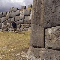 A traveler walks by huge, intricately hewn stone blocks at Sacsayhuamán, an Inca ruin near Cuzco, Peru, that was the site of one of their last decisive battles with Pizzaro and the Spanish conquistadors.