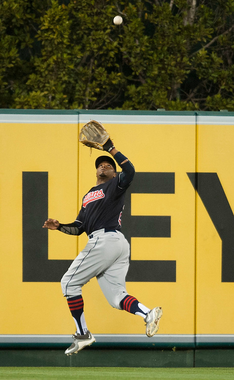 The Indians' Rajai Davis leaps for an Albert Pujols fly ball in the fourth inning Friday at Angel Stadium. <br /> <br /> ///ADDITIONAL INFO:   <br /> <br /> angels.0611.kjs  ---  Photo by KEVIN SULLIVAN / Orange County Register  -- 6/10/16<br /> <br /> The Los Angeles Angels take on the Cleveland Indians Friday at Angel Stadium.