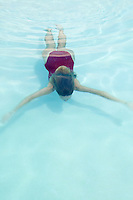 woman in red bathing suit swimming under the water in a pool with blue water