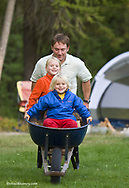 Reid Sabin gives kids Eilse and Chase a ride in the wheelbarrow at campsite near Whitefish Montana model released