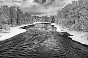 Saranac River, Adirondacks, NY.<br /> <br /> It had barely stopped snowing, and sunrise was still a ways off as I looked downstream on the Saranac River.   Running through this winter corridor, the river hit this shallower streambed that created riffles and added definition against the nearly featureless white banks.