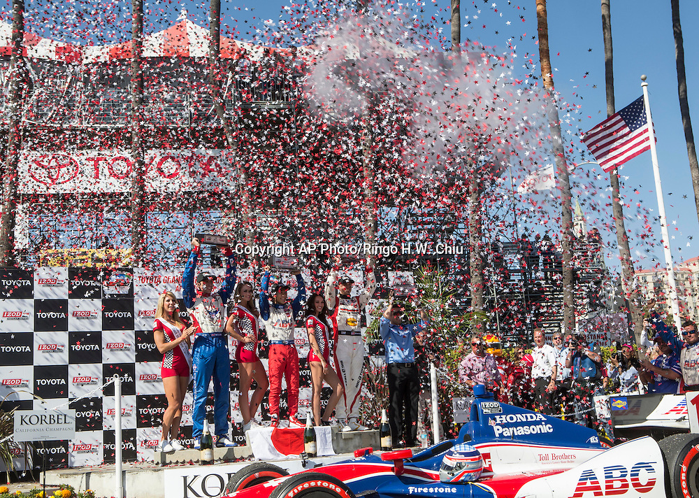 From left, Justin Wilson (19) of England,  Takuma Sato (14) of Japan and Graham Rahal (15) celebrate with their trophies on the podium after the IndyCar Series' Toyota Grand Prix of Long Beach auto race, Sunday, April 21, 2013, in Long Beach, Calif.  (AP Photo/Ringo H.W. Chiu) (AP Photo/Ringo H.W. Chiu)..