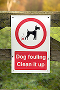 Sign saying Dog fouling Clean it up on fence