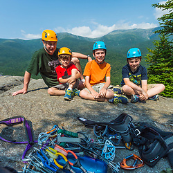 Writer Brad Tuttle with his sons (from left to right) Nate, Will, and Owen, at the top of Square Ledge in New Hampshire's White Mountains. Mount Washington is in the distance.