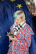 A young woman wearing a Union Jack rain coat looks at her mobile phone outside the Houses of Parliament the day after Theresa Mays crushing defeat over her Brexit deal on the 16th January 2019 in London in the United Kingdom.