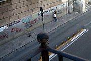 A women walks down Via Maqueda past a wall covered in graffiti, Palermo, Italy