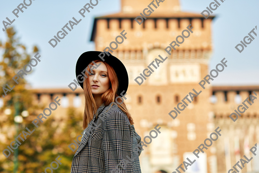 Model pose for a portrait with the Castello Sforzesco at the background in Milano Italy.