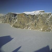 NUNAVUT, Canada. Unnamed cliffs tower above frozen Quernbiter Fjord on northern Baffin Island, north of Arctic Circle.