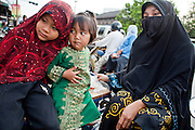 """Sept. 24, 2009 -- PATTANI, THAILAND:  Children with their mother in traditional Muslim dress in Pattani, Thailand. Thailand's three southern most provinces; Yala, Pattani and Narathiwat are often called """"restive"""" and a decades long Muslim insurgency has gained traction recently. Nearly 4,000 people have been killed since 2004. The three southern provinces are under emergency control and there are more than 60,000 Thai military, police and paramilitary militia forces trying to keep the peace battling insurgents who favor car bombs and assassination.   Photo by Jack Kurtz / ZUMA Press"""