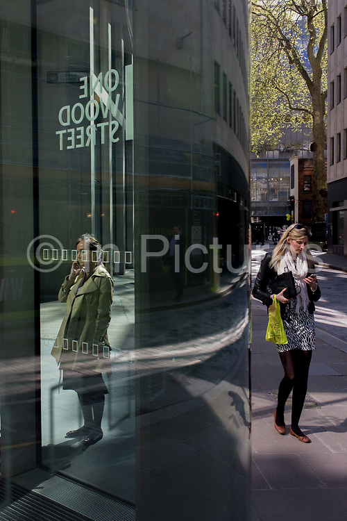 Women use smartphones outside a corporate office entrance with city reflections in glass. As strangers, the ladies don't know each other and the one on the right walks past the other, oblivious to her presence, busily texting or dialling a number on her phone. The address shown in reverse on the window is One Wood Street in the capital's financial heart - the City of London, known as the Square Mile, founded by the Romans in AD43. Wood Street EC2, was where wood was once sold in medieval times, mentioned in the writing of Charles Dickens but devastated during WW2. The giant plane tree in the background rises over 70 feet high and fated in the annals of London history for almost 600 years.