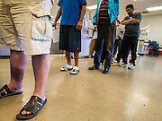 05 NOVEMBER 2013 - PHOENIX, AZ: People wait in line for food assistance at St. Mary's Food Bank in Phoenix, AZ. Demand at St. Mary's has continued to increase even as government assistance is reduced. Over the summer, St. Mary's Phoenix location provided emergency food for 300 - 400 families per day. They are currently supporting about 600 families per day. Part of the increase is seasonal but a large part of it is no clients coming to the food bank for the first time. More than 1.1 million Arizonans who use the Supplemental Nutrition Assistance Program, known as food stamps, saw their benefits reduced Friday, Nov. 1, in a long-planned national cut that was tied to the economic stimulus which was a part of the American Recovery and Reinvestment Act. The cuts imposed last week range from $11 a month for a single recipient to $65 or more for large families. Many of SNAP receipients already use food banks to supplement their government assistance and the cuts in the SNAP program are expected to increase demand even more.   PHOTO BY JACK KURTZ
