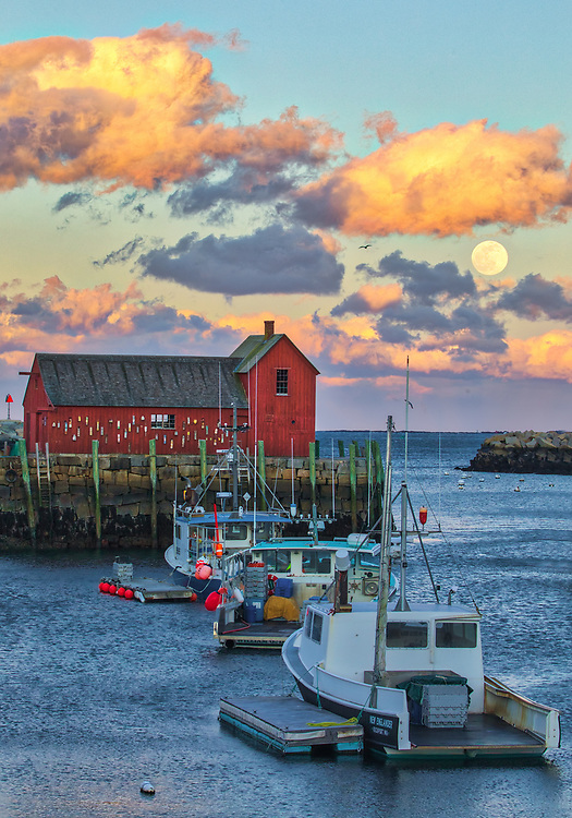 New England photography of the famous red fishing shack Motif Number One in Rockport, MA on Cape Ann with a full moon rising was photographed on a cold night. The historic landmark is known throughout New England as Motif #1, so called because it is the most often painted building in America.<br />