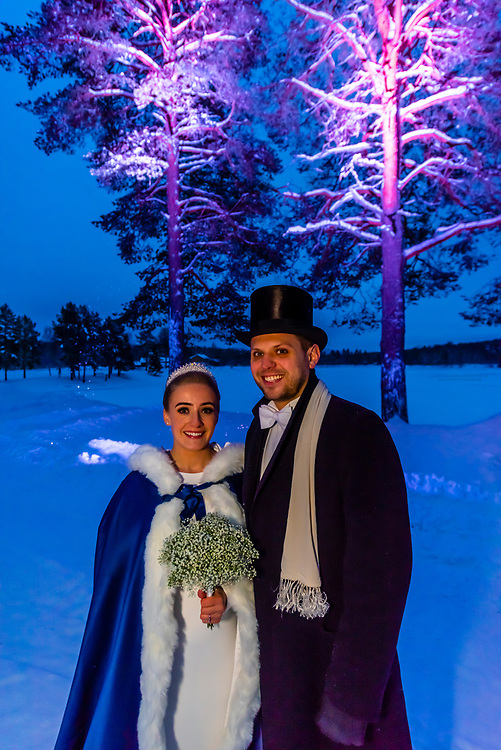 A Norwegian newlywed couple stand outside in a  winter wonderland before their wedding reception, Trysil, Norway.