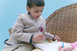 Little boy drawing with crayons in a book,