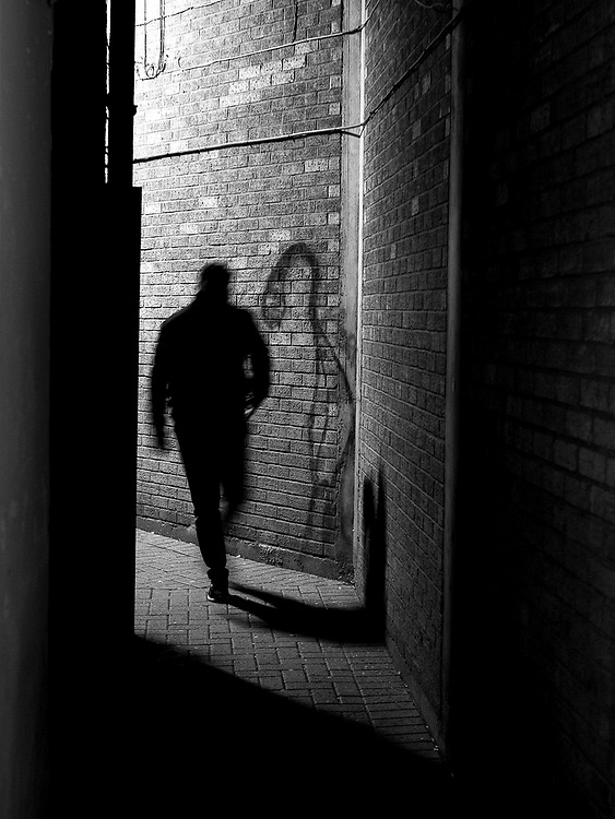 A person walks down an alley onto the high street, casting a shadow onto the wall. Cheltenham, England on the 15th October 2020