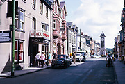 People and cars in street by Lion Royal hotel in Rhayader, Radnorshire, Powys, central Wales in 1964