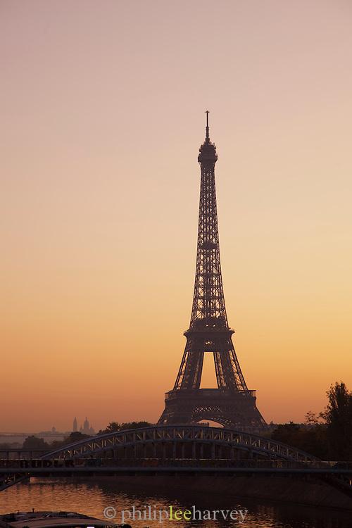 The iconic Eiffel Tower at dawn from Pont de Grenelle, seen across Pont de Bir-Hakeim in Paris, France