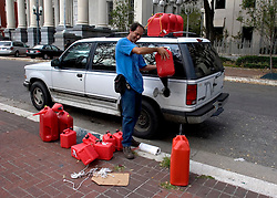 10 Sept 2005. New Orleans, Louisiana. Hurricane Katrina aftermath. <br /> Bloomberg News journalist Oscar Sousa fills his car for another days reporting on the catastrophic events following the storm.<br /> Photo; ©Charlie Varley/varleypix.com