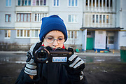 Yaroslav, 10, is filming with his UNICEF video camera near the provisional home where he resides with his mother Olga, 36, as internally displaced persons. (IDPs) Yeroslav is taking part to the UNICEF-sponsored One Minute Junior project for internally displaced persons (IDPs), carried out by the local NGO 'Ukrainian Frontiers' in the city of Kharkiv, the country's second-largest, in the east. The conflict between Ukrainian army and Russia-backed separatists nearby, in the Donbass region, have left more than 10000 dead since April 2014, including over 1000 since the shaky Minsk II ceasefire came into effect in February 2015. The approximate number of people displaced by the conflict is 1.4 million as of August 2015. Yeroslav's mother, Olga, is also a participant to a different project of 'Ukrainian Frontiers', called 'Self-Employment', first as a beneficiary, and now as a paid hotline coordinator for people seeking jobs and formation courses.