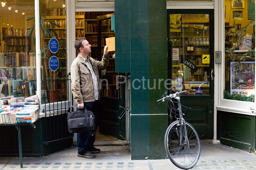 A man searches for a book outside a shop in Cecil Court, London, UK<br /> Cecil Court specialises in rare and antiquarian bookshops, antique prints and ephemera dealers